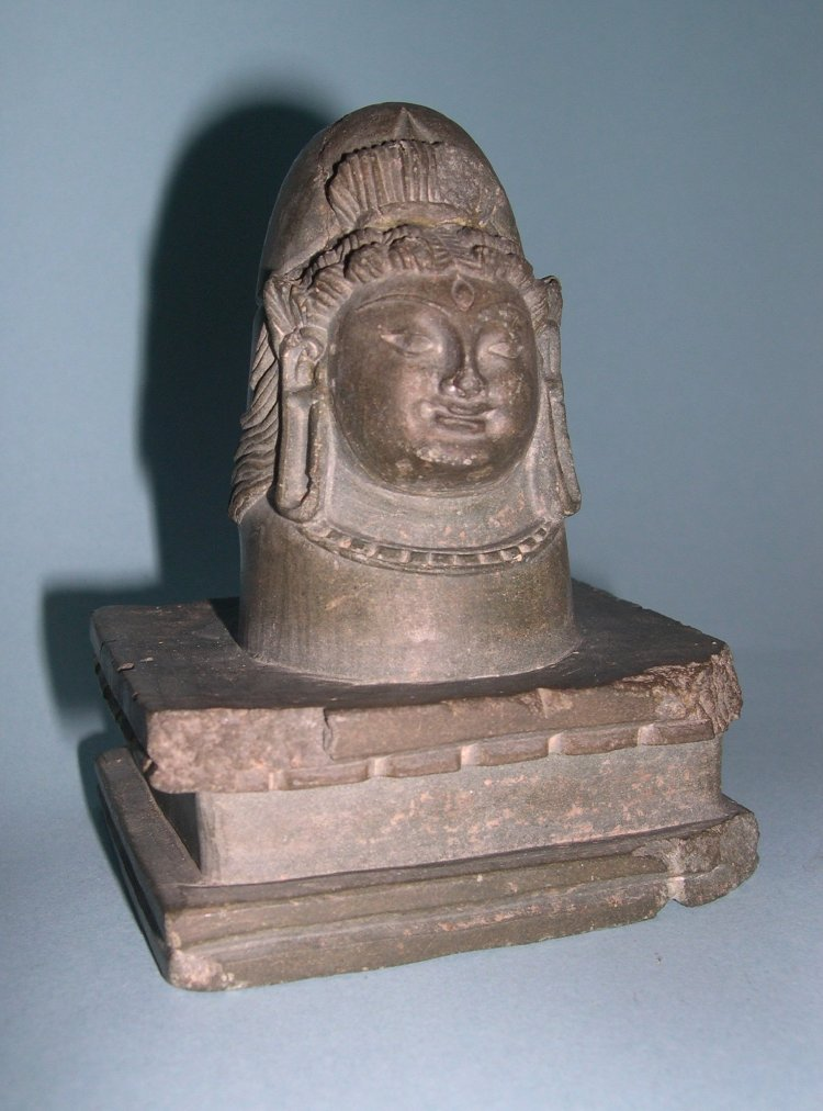 Liṅga, with face of Śiva. Made of stone (schist).  7th C - 9th C