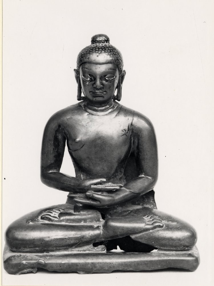 A figure of the Buddha seated in padmāsana, his hands folded on his lap in dhyānamudrā; cast in bronze with copper and silver inlay.  Despite its modest size this bronze has a monumental aspect with a fullness of face and body due to the influence of Gupta modelling absorbed by the art of Kashmir. While it resembles seated Buddhas in central and even eastern India on account of this common influence, its distinctively regional features appear in the shape of the head, the hairline and the upward tilt of the eyes. The copper inlay of the lips and silver in the eyes, like the flap of the robe hanging from the left shoulder, are Indian medieval characteristics; inlay became progressively commoner. The damage on the image may be due to casting faults.  8th C