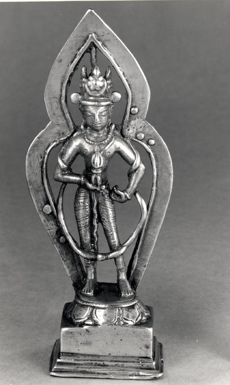Standing figure of Vajrasattva, cast in a copper alloy, with a pointed halo, broken and repaired with straps and rivets. 15th C. Found in Tibet