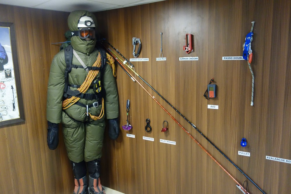 A low temperature high Altitude all Weather suit. along with different climbing aids displayed on the Wall.