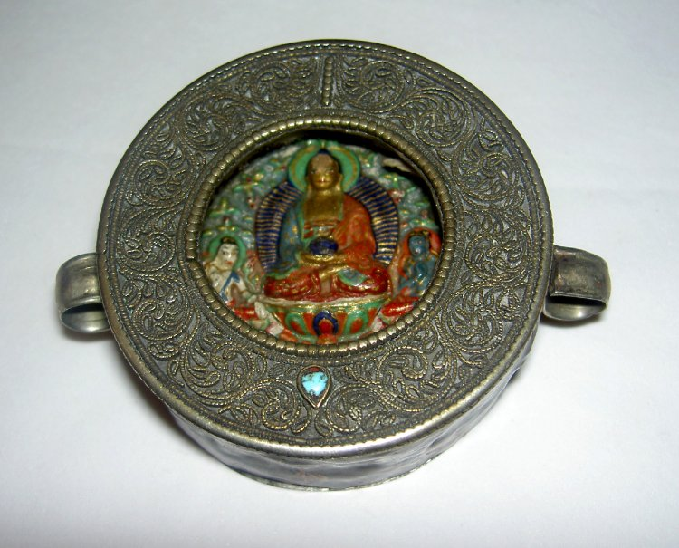 Amulet-box. Circular amulet-box made of silver with wirework decoration; inside a painted plaque with with a seated Buddha.-ladakh