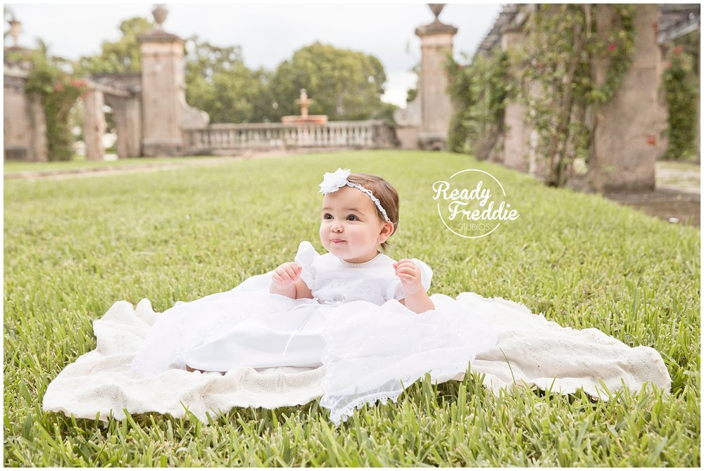 One year old sitting down in her baptism gown