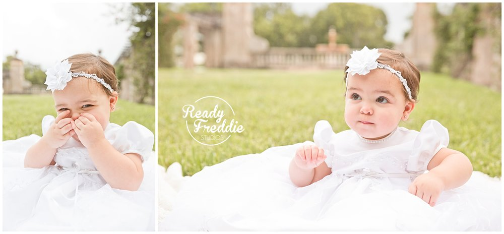 1 year old girl making funny faces in her baptism dress