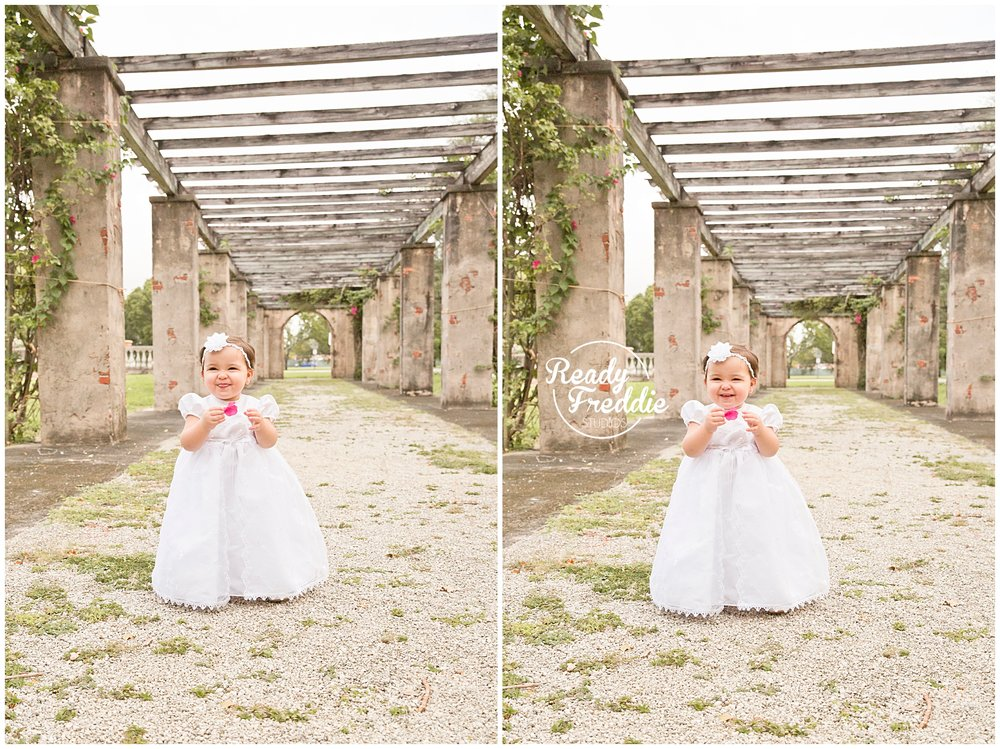 Girl is baptism gown taking baptism pictures