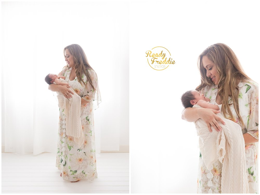 Beautiful pose of mom holding newborn baby standing in front of a window