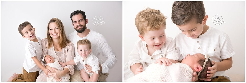 3 kids with parents and siblings looking at newborn baby in all white miami photo studio