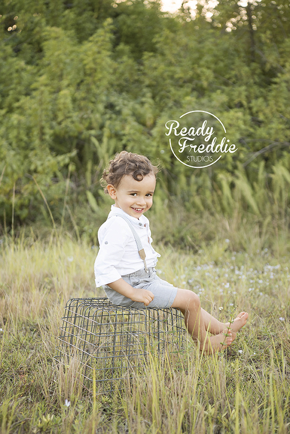 Toddler in a field smiling at the camera in Miami Florida