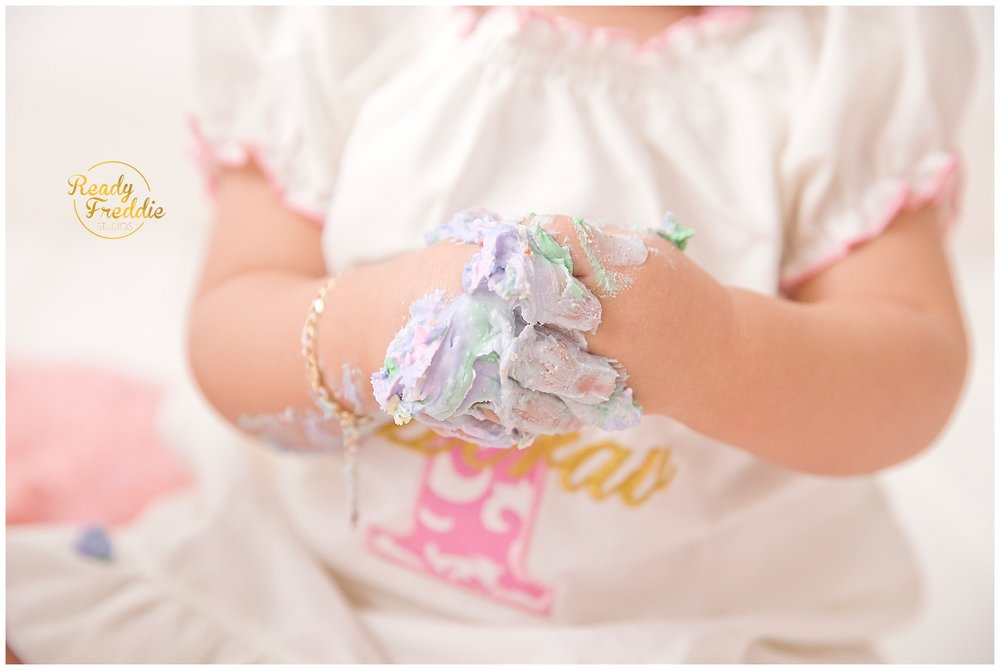 baby hands filled with cake during cake smash photography session in miami fl