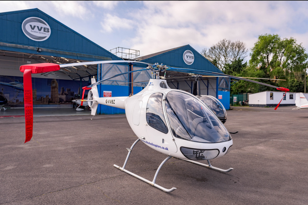 Cabri G2 helicopter parked outside hangar