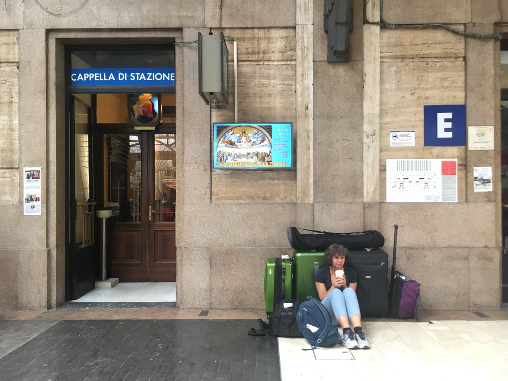 Anna drinking a coffee while looking after all of our bags at Milan's Central Station. We happened to be sitting by the station chapel, hoping that's a good sign…