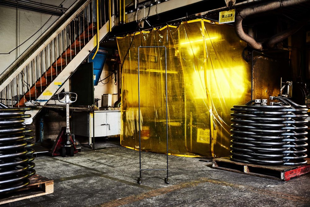 GARMENT RACK   省スペース仕様のハンガーラック(コートハンガー)。部屋のちょっとしたスペースに、頻繁に着用する衣類を収納できる家具が欲しくて製作しました。奥行・幅どちらも30cm程度で、ちょうど本棚や飾り棚の横に収まるサイズです。  工業用製品に使用される金属棒をそのまま曲げ・溶接してあるので、組み立て家具のような不安定さはありません。また一本脚のコートハンガーのように重量の偏りで不安定になることもありません。生活感を漂わせるインテリアにならないよう塗装にもこだわり、金属独自の武骨でミニマムな風合い、ハンドメイドならではの手作業の名残りを生かしました。薄手アウターは10~12着、冬用厚手アウターは7~8着の収納が可能です。