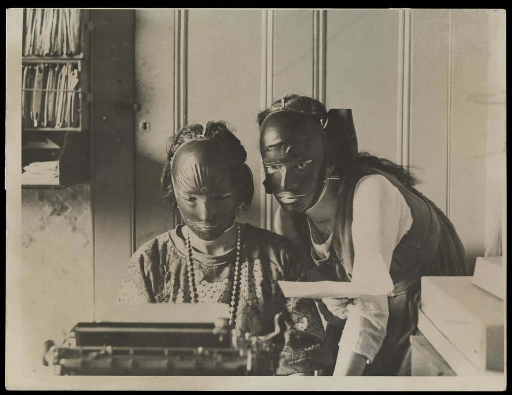 Rubber beauty masks, worn to remove wrinkles and blemishes; modelled by two women at a typewriter (1921)