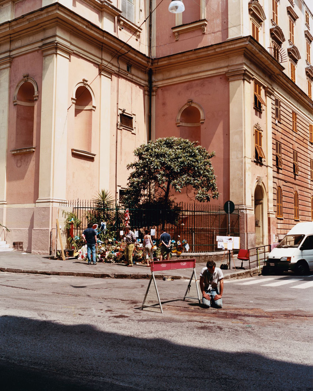A man kneeling at the spot where Carlo Giuliani lost his life, Piazza Alimonda, Genoa, 21 July 2001