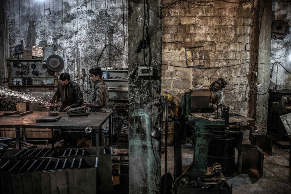 - Syrians work at a factory producing wood-burning stoves,known locally as a