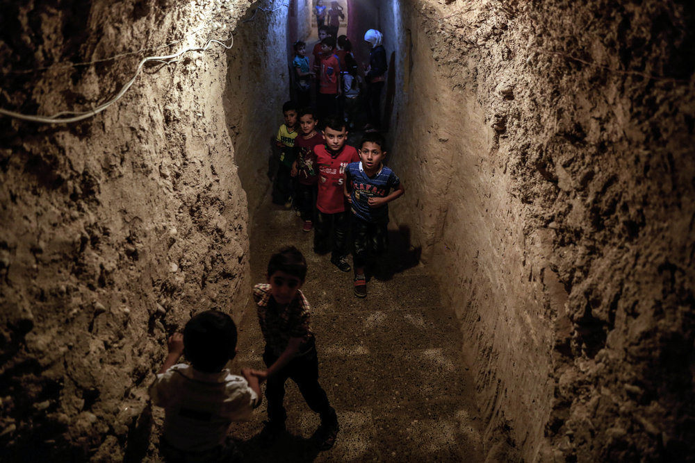 - Children play in an underground playground built to protect them from shelling.