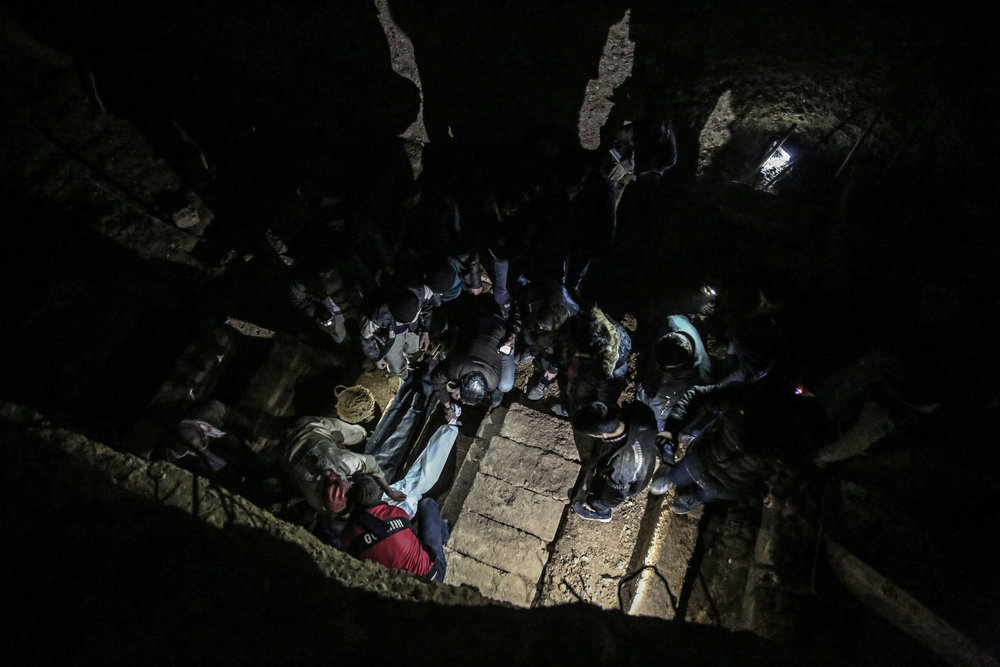 - Syrian men gather to bury the bodies of a family in a layered underground cemetery.