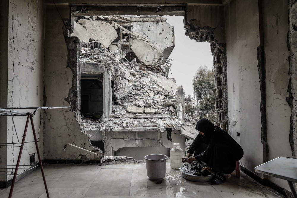 Syrian Umm Mohammed, washes laundry at her destroyed home in the rebel-held town of Douma.