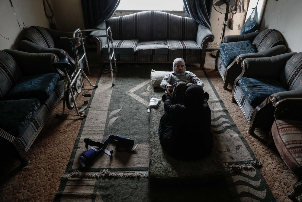 Um Mohammed, performs rehabilitation exercises with her war-injured husband at their home.