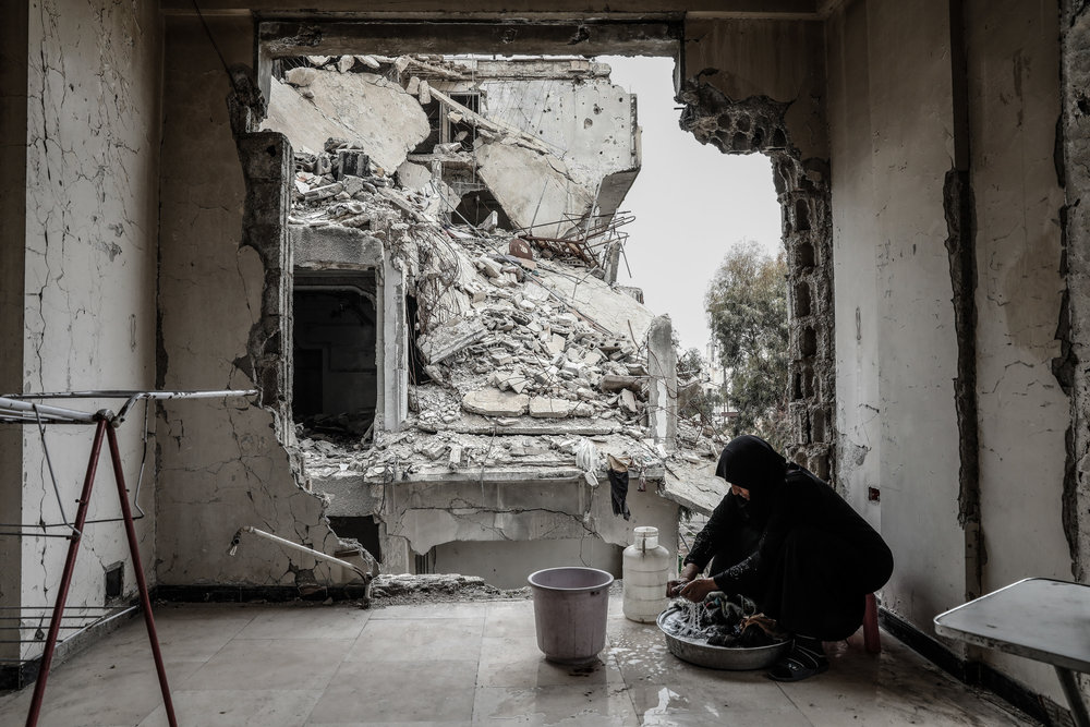 - Umm Mohammed, washes laundry at her destroyed home.