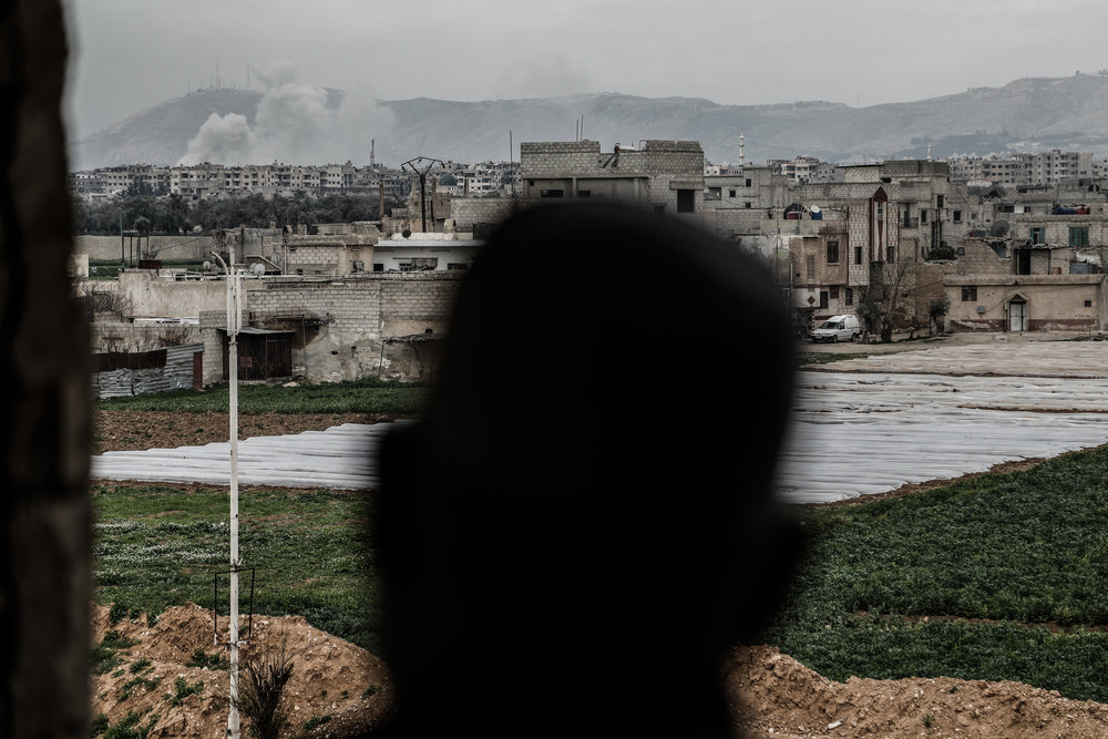 - Abu Mohammed, watches smoke billowing from his home following a government air strike.