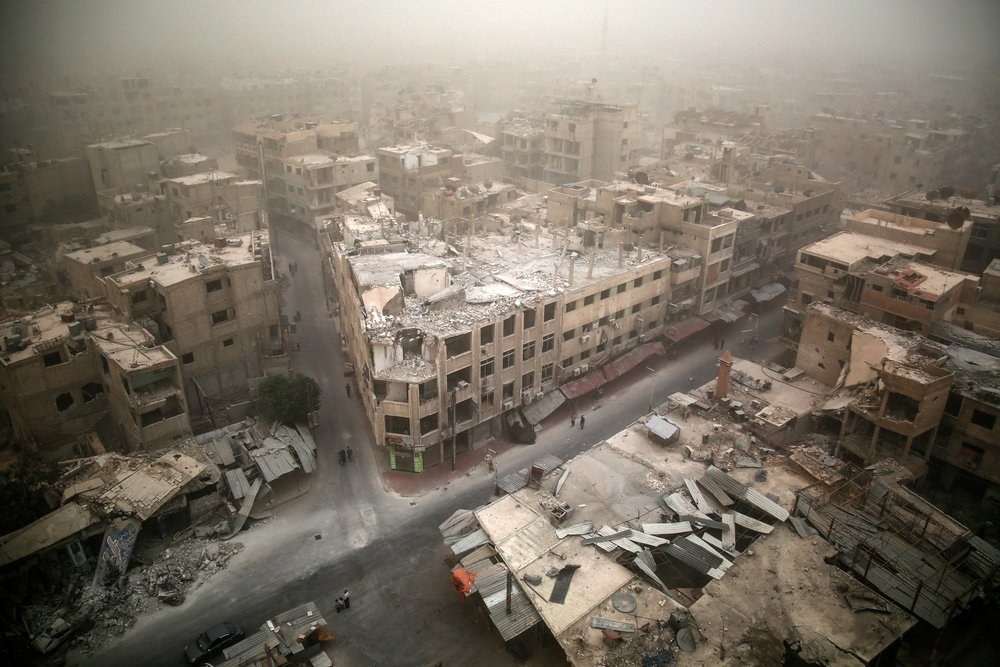 A picture shows a general view of damaged buildings in the city of Douma, east of the capital Damascus as a sandstorm blows over the city.