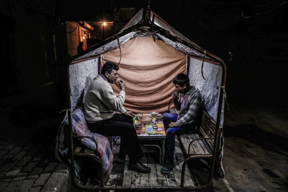 - A man and child sit together and have a meal in a makeshift stall at night, in the city of Douma.