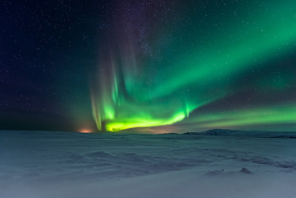 Northern Lights dancing over snowy landscape. Photo: Surangaw