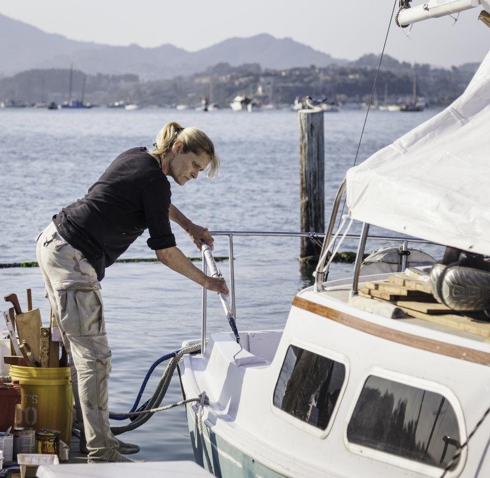 """Bianca Vonc - Bianca habite seule sur son bateau depuis plus de 12 ans maintenant. Ici, elle est en train de repeindre en blanc le cockpit de l'un de ses 3 bateaux. Bianca m'explique que la loi ne l'autorise pas à vivre tous les jours à bord. Elle passe donc 3 jours par semaine sur l'eau et 3 jours dans un camping-car stationné à côté de la marina. Elle m'apprend que les gens comme Neil, Ron ou encore Len sont appelés les """"grands-pères de la marina"""" et ont le droit de vivre à bord en raison de leur ancienneté au sein de la communauté."""