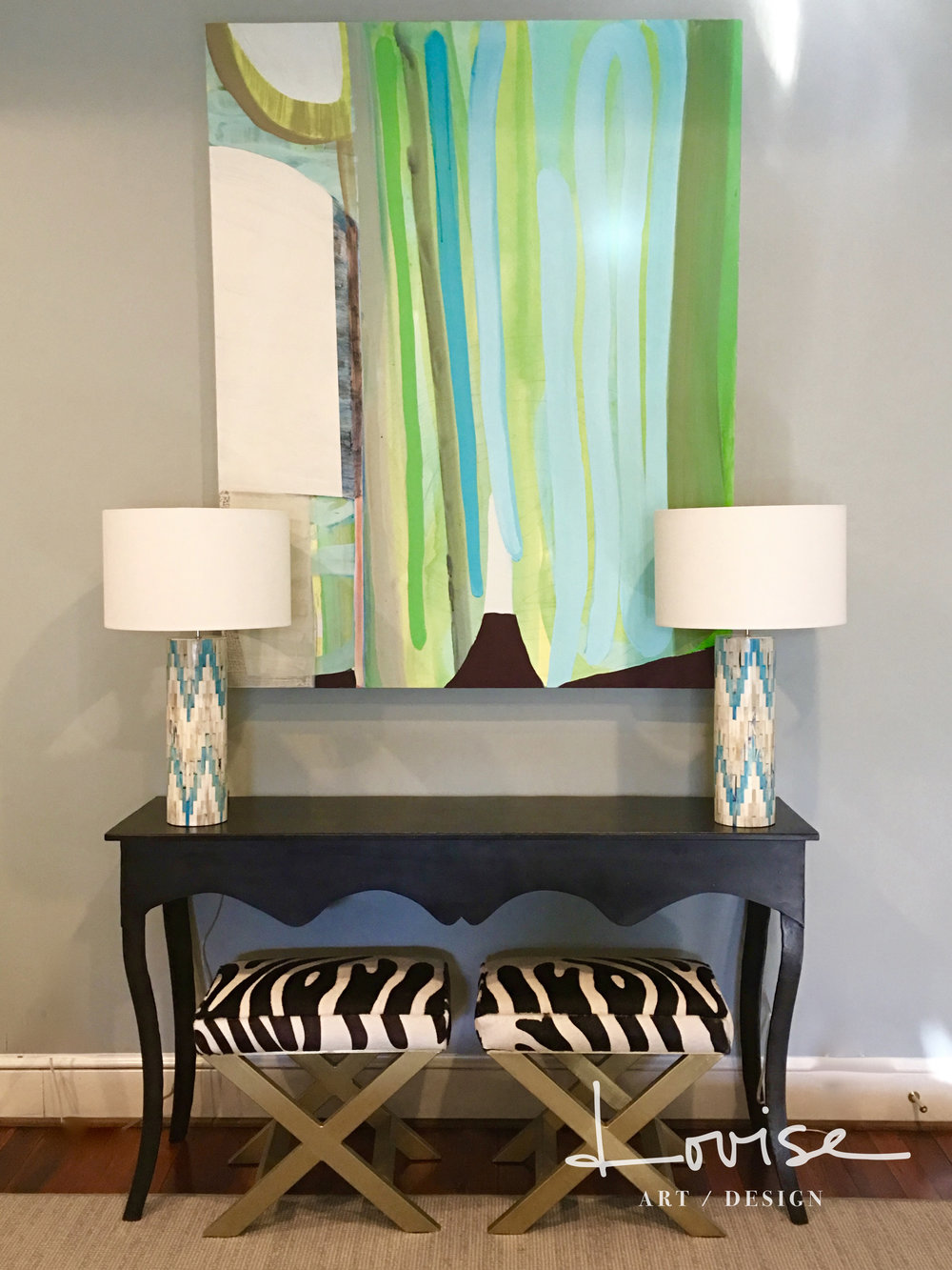 Black console with bone inlay lamps and abstract painting