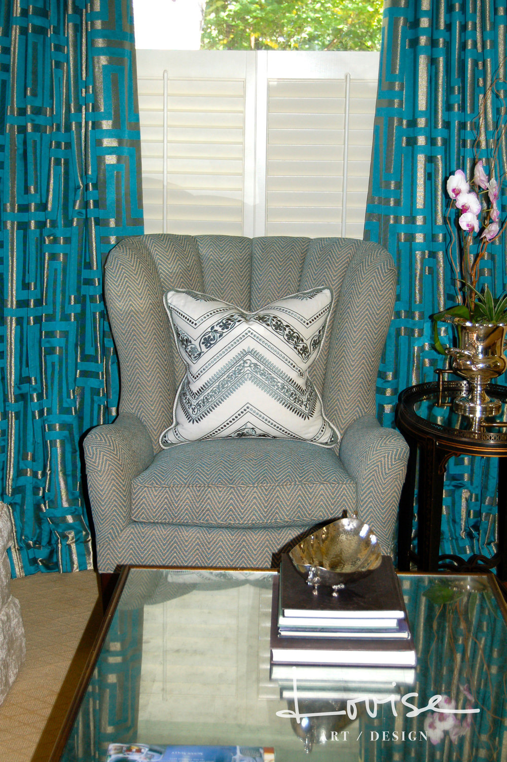 Metallic Greek key draperies and turquoise chevron wingback chair