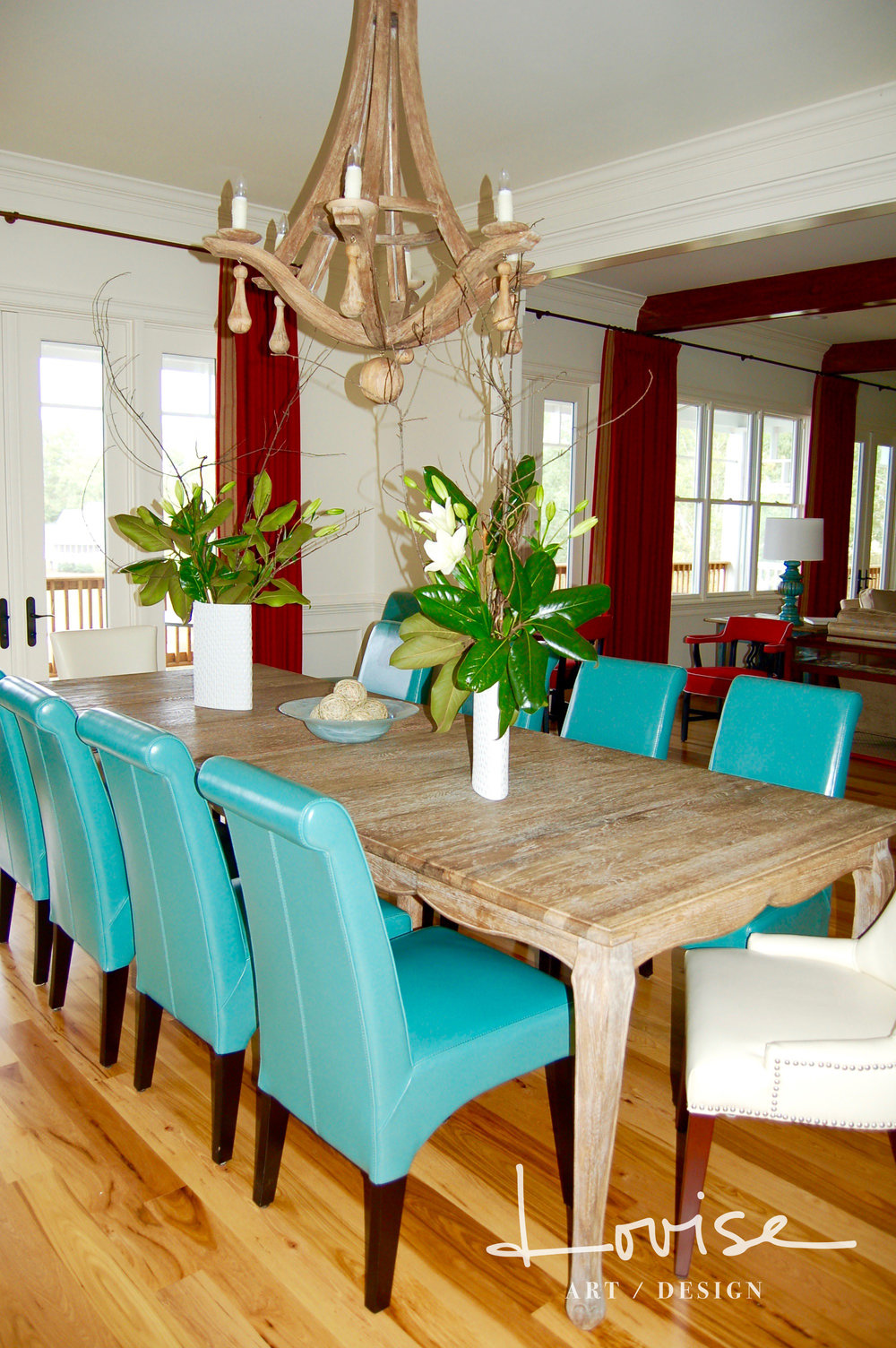 Casual dining table with turquoise leather chairs and wood chandelier