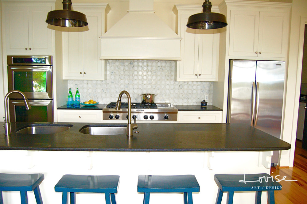 Casual kitchen with black countertops, double sinks, marble backsplash and blue stools