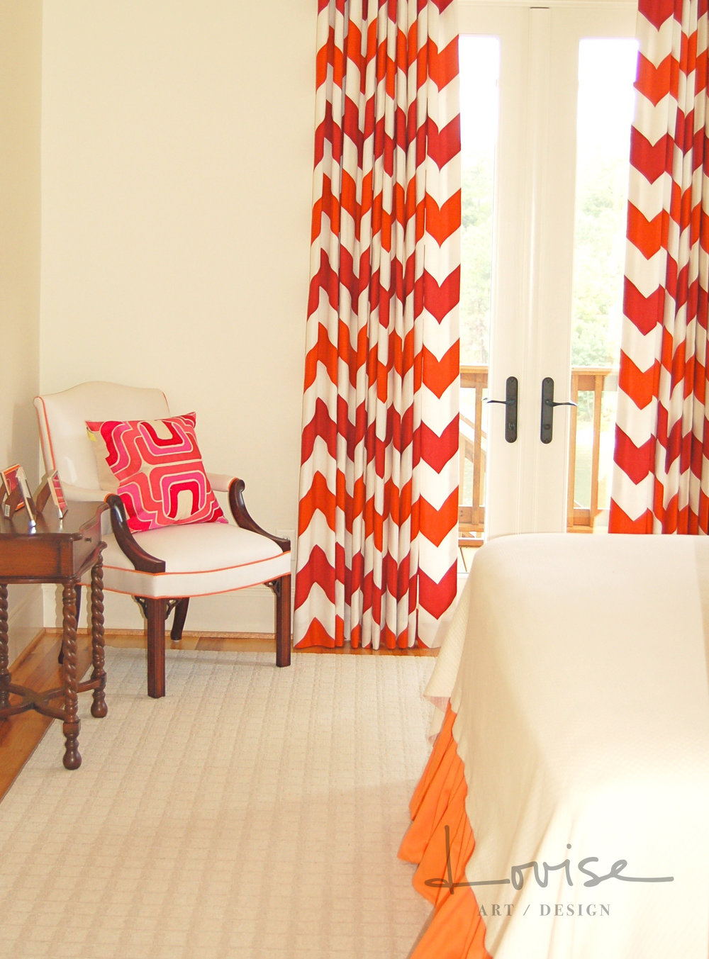 Lake bedroom with red and orange chevron draperies