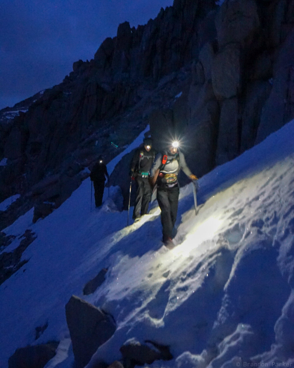 Alpine starts mean you hike in the dark. ACB leading a group across the snow chute.