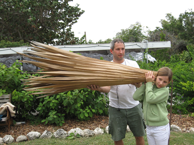 "Large palm Leaf trumpet (original version), double leaf construction with split rattan interior ribs and reinforcement with palm fiber and sponge, sealed with oils and resins, 67"" L x 16"" largest diameter.   Child listening, aided by friend."