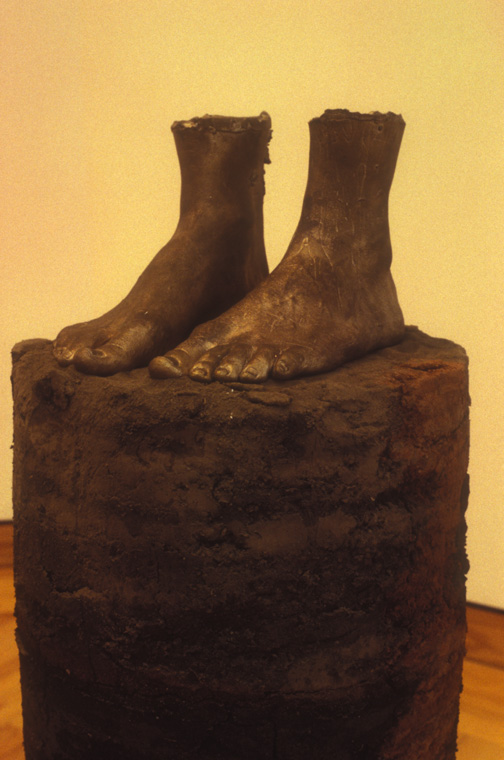 """CORE SAMPLE: SELF PORTRAIT  1994 earth from every place I've lived, 1"""" equals 1 year, earth from Missouri, Louisiana, Illinois, Alabama, Minnesota, Maine, Missouri,  Glue, life cast bronze of my feet, cylinder, 43"""" x 12"""", detail."""
