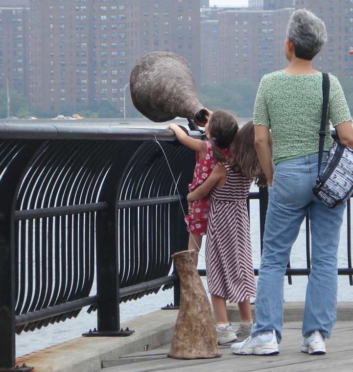 Child lifting child to see the framed view of Brooklyn Bridge.