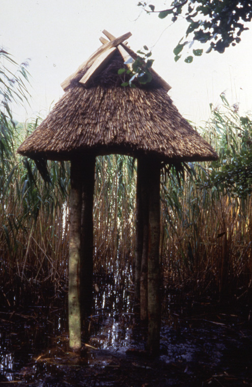 "Sited in edge of damaged lake, North/South orientation. Wood thatched local reeds and heather, 9'9"" x 4'8"" x 8 H."