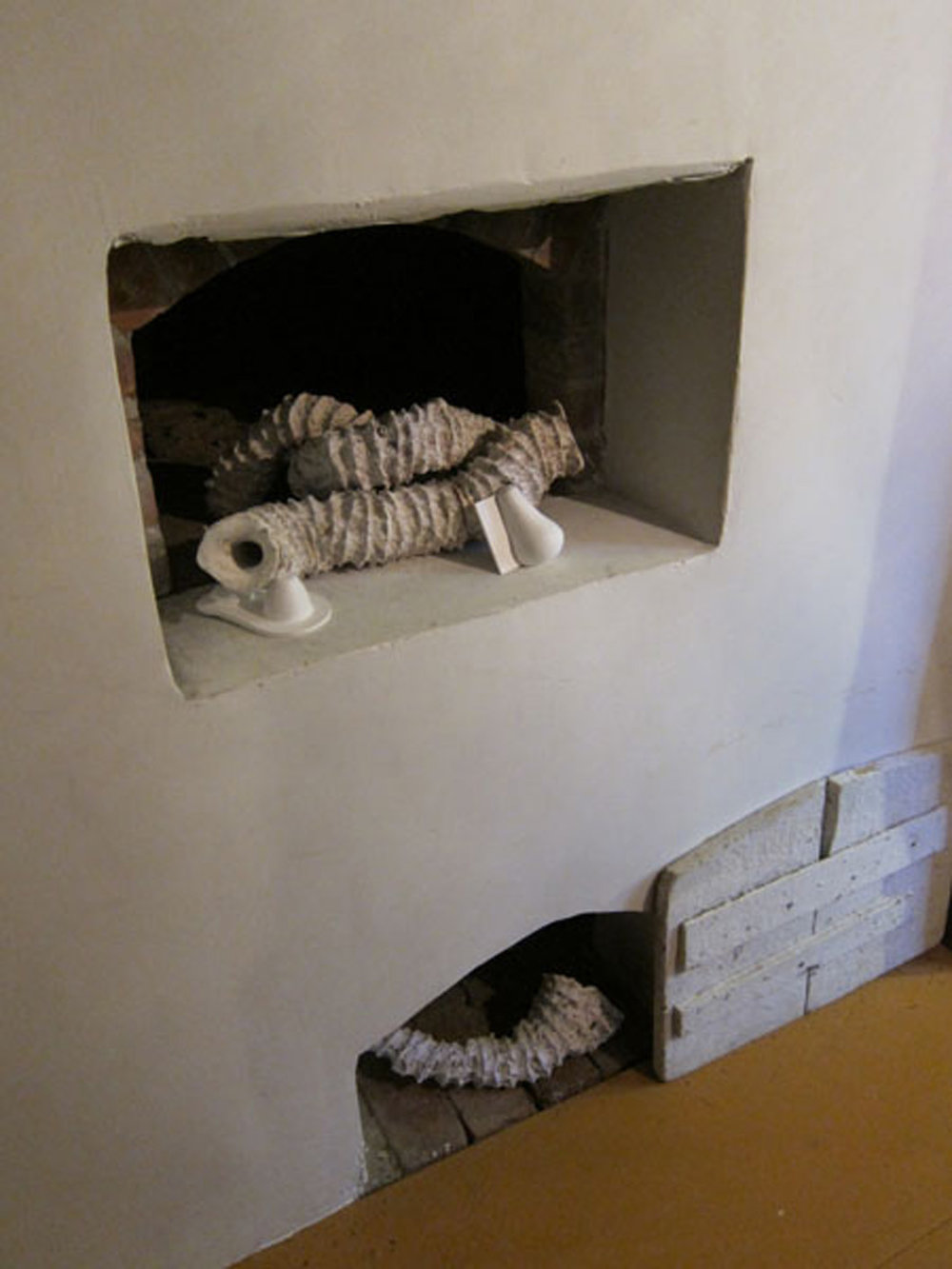 """Seemingly Unconnected Events: Warming  2011 Wentworth-Coolidge State Historic Mansion Portsmouth, NH  Installation in warming niches off the sunken brick kitchen near visitors entrance.  Plaster casts of organic forms with casts into consumer goods packaging, """"Seaworms"""" 2-3"""" diameter x 17"""" shortest and 37"""" longest; consumer goods life sized."""