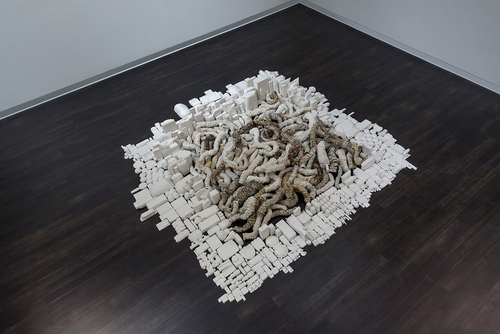 """Seemingly Unconnected Events Cubed (V3)  2007- 2014 (ongoing)  DETAIL, Hundreds of plaster casts of organic forms interwoven and interconnected with consumer goods casts, 4 x 4 x 40"""" highest point  Installation at Epsten Gallery, Village Shalom, metropolitan Kansas City, MO, 2014   Photo: E.G. Schempf"""