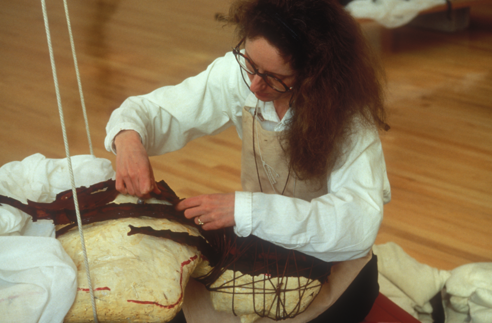 ACTION: CONSTRUCTION OF GUARDIAN  1994  Plaster life cast, kelp backed with natural latex and waxed felt, needles, thread, water, custom sand bags, detail of McCoy sewing during Under the Skin at Williams College Art Museum, Williamstown, MA.