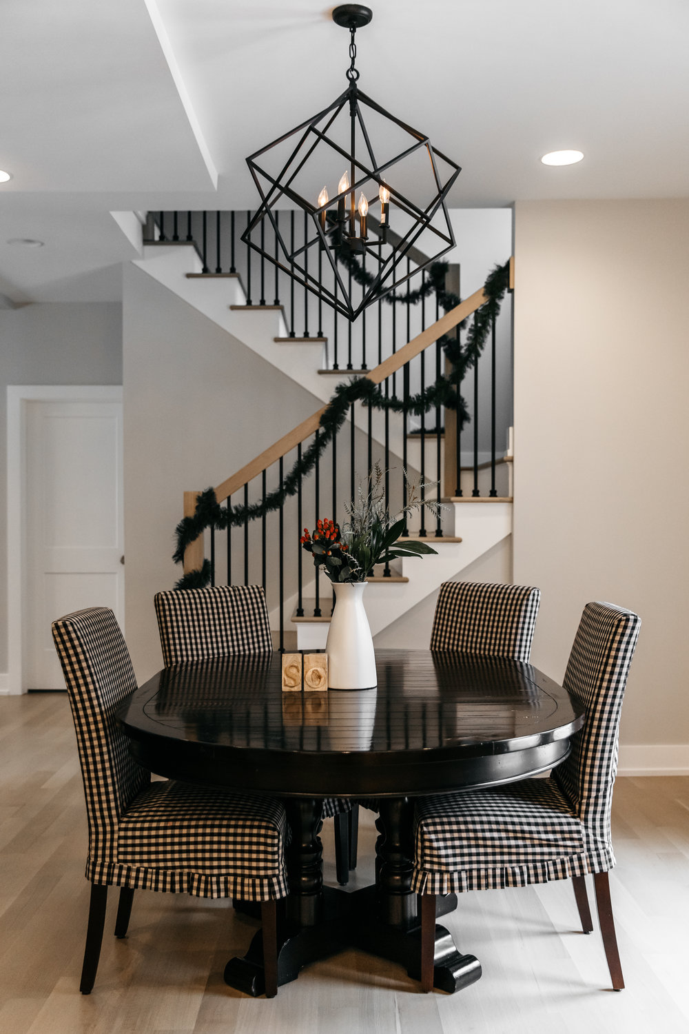 Dining table with floral centerpieces and garland wrapped staircase
