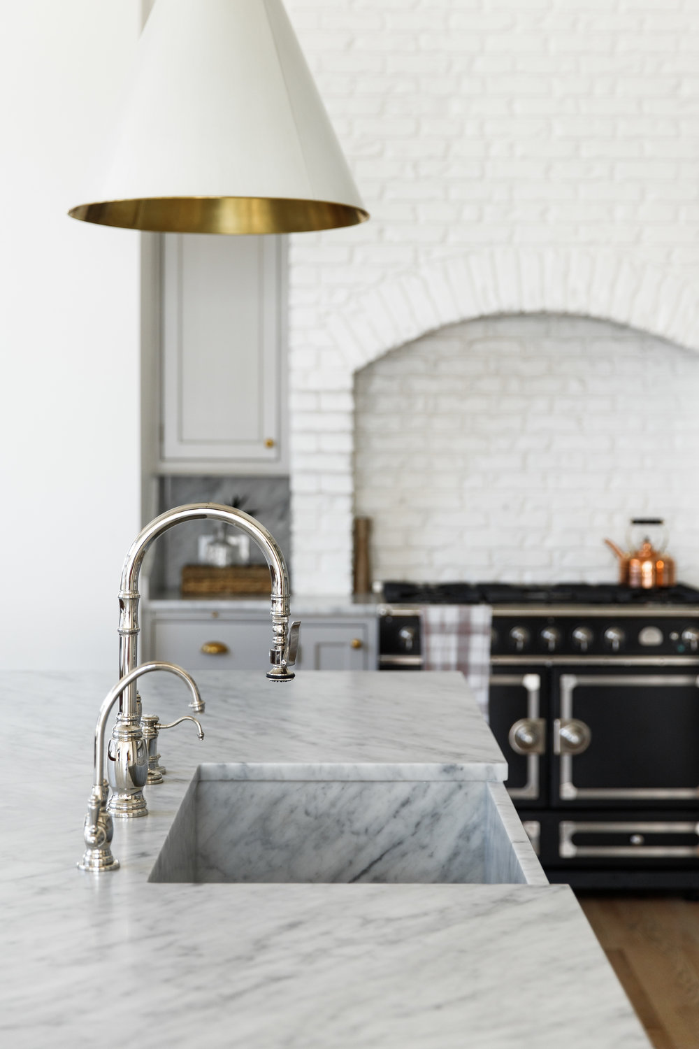 Light gray cabinets with gold hardware, LaCornue range and full height honed Carrara Marble countertops, backsplash and apron front sink.