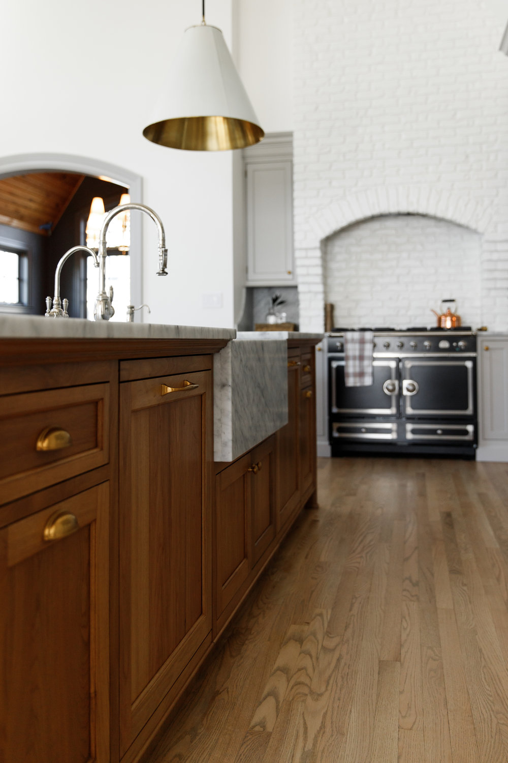 Bleached walnut island, honed Carrara Marble countertops with apron front sink and stained red oak floors.