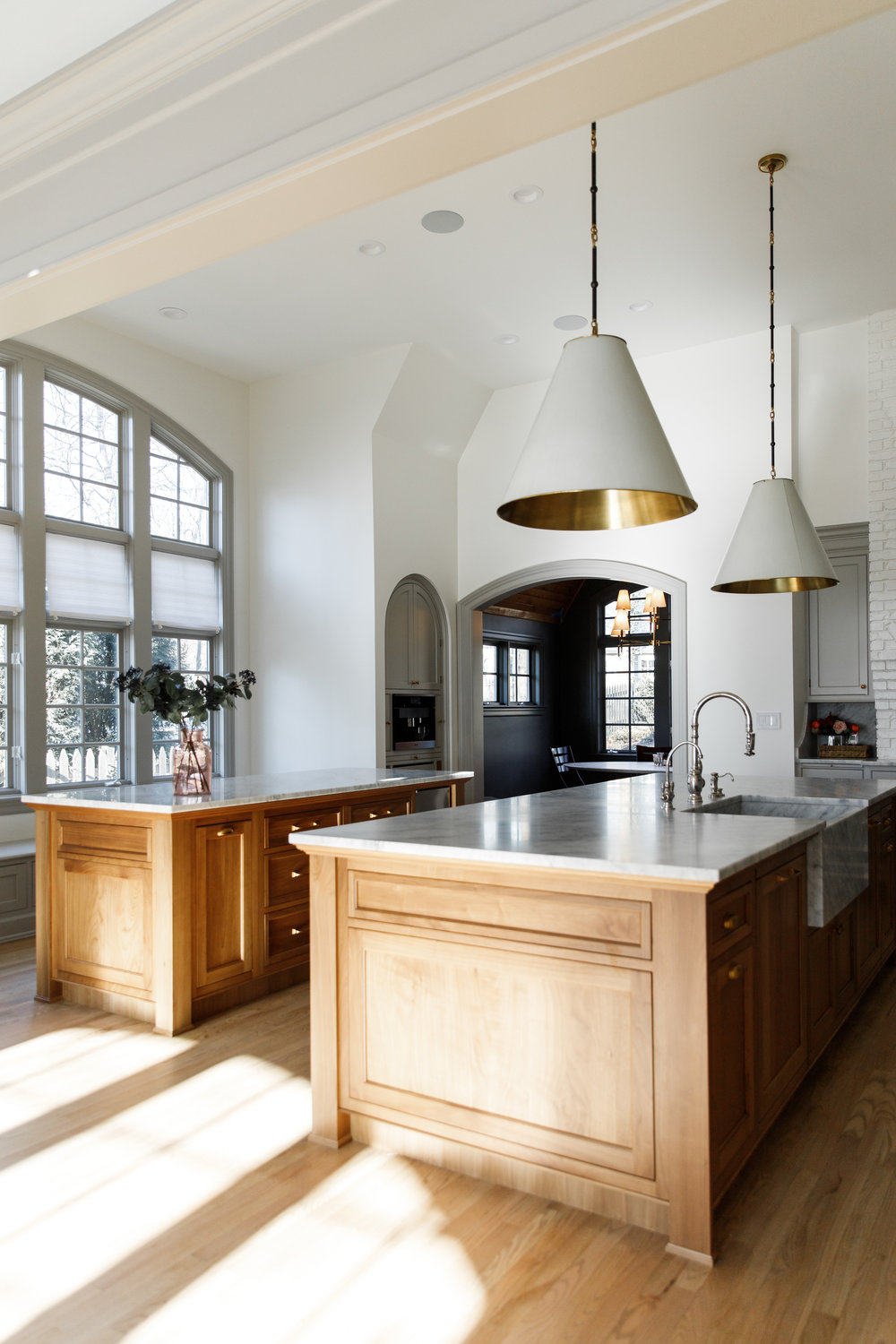 Bleached walnut double island, honed Carrara Marble countertops with apron front sink and stained red oak floors.