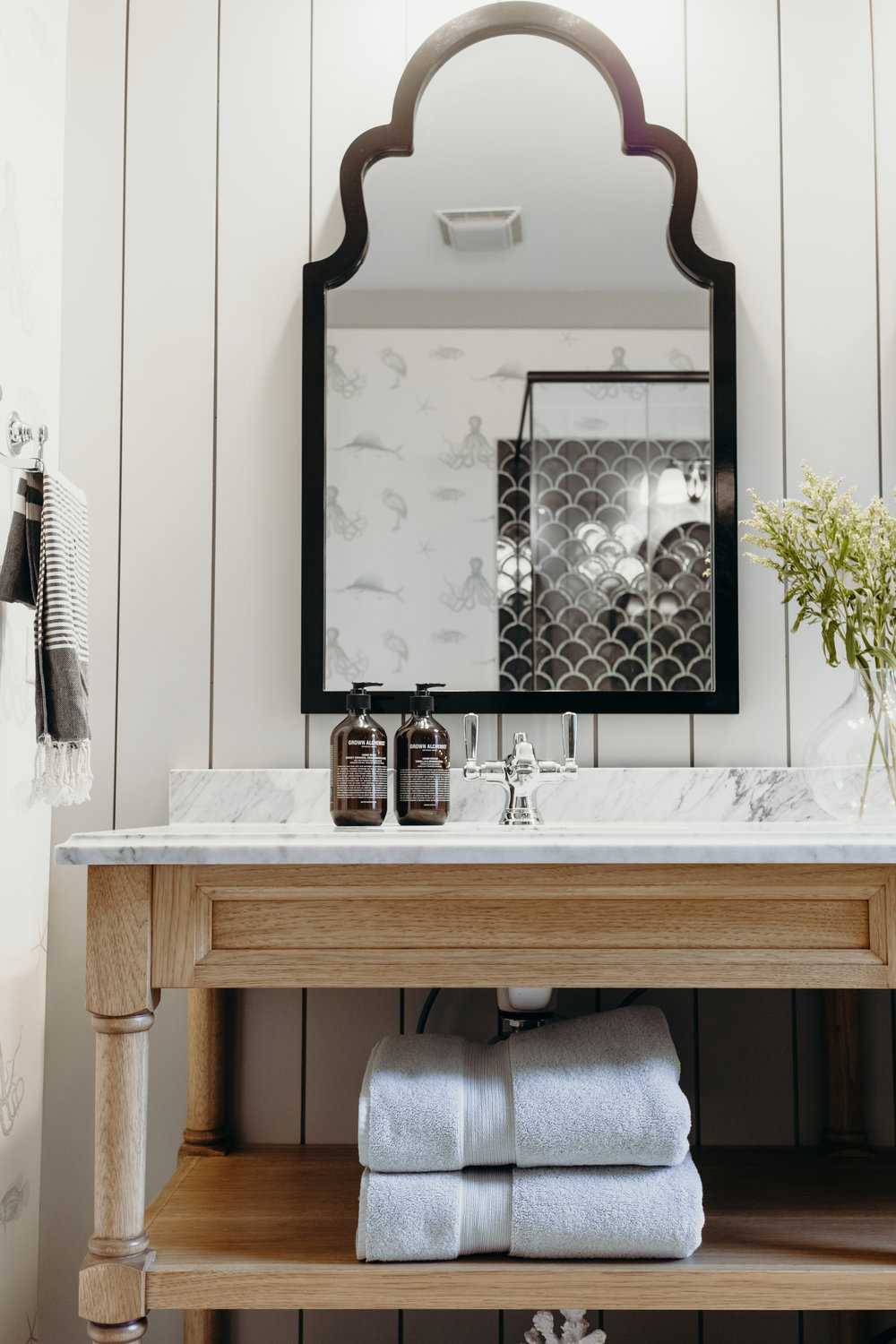 open shelf vanity with black vintage mirror and shiplap accent wall