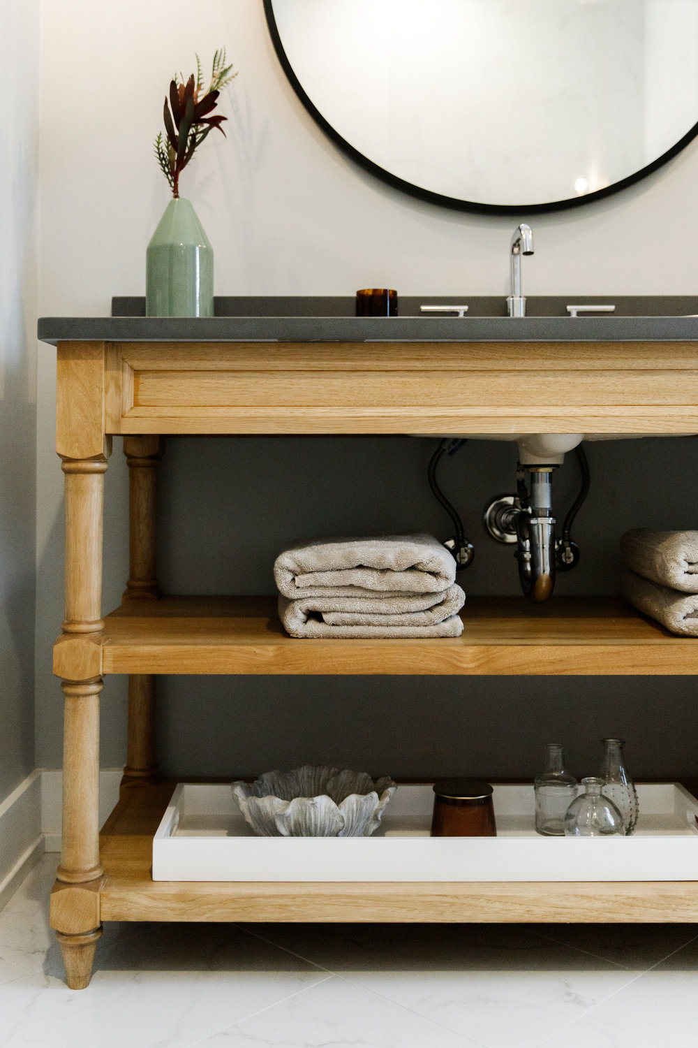 Vanity with open shelves and exposed plumbing with chrome hardware