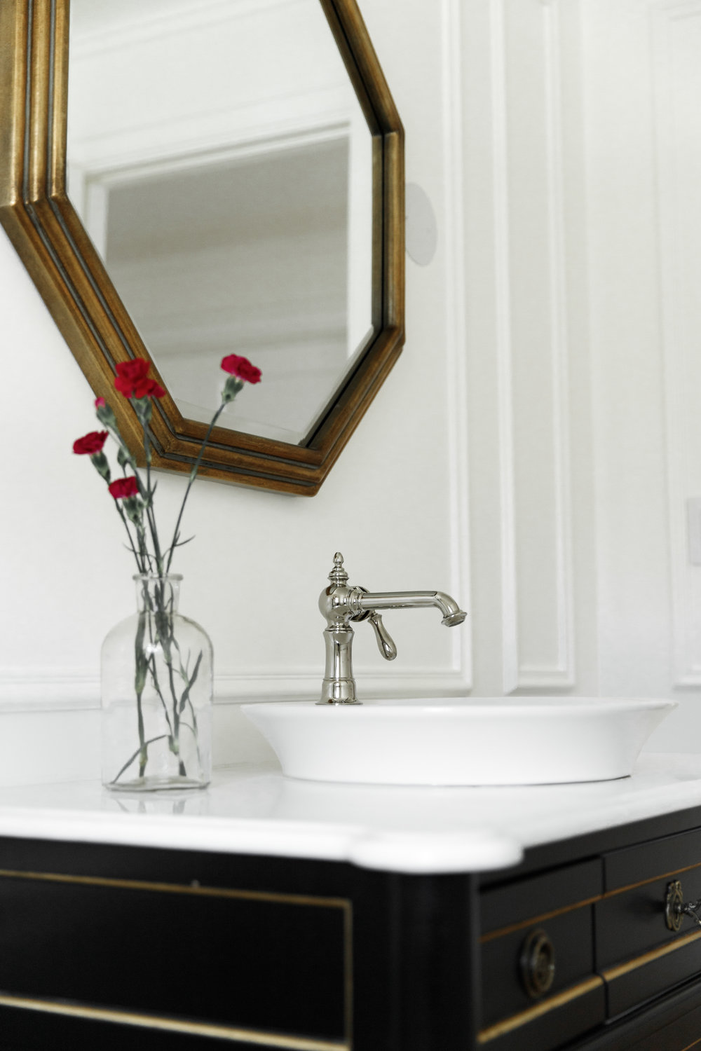 Gold octagon mirror and black vanity with chrome hardware