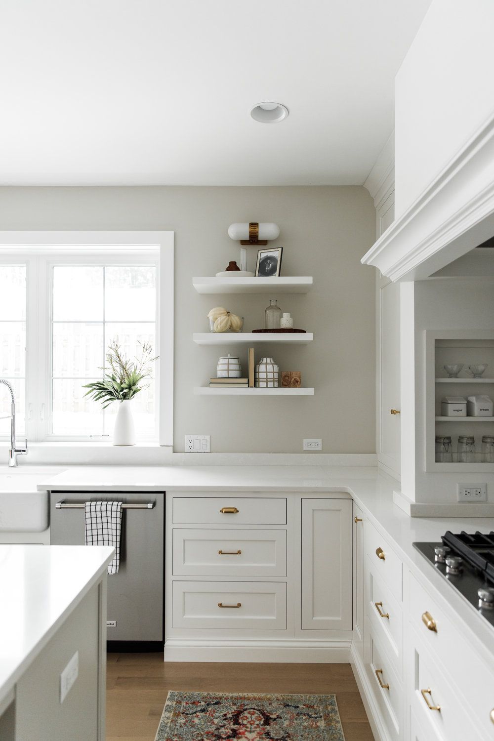 White kitchen with brass hardware and oak floors