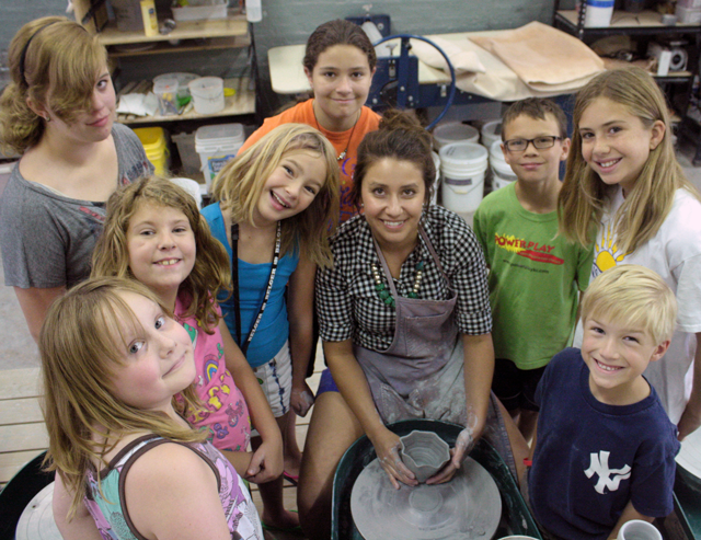 Catie-Miller-teaching-kids-on-the-potters-wheel.png